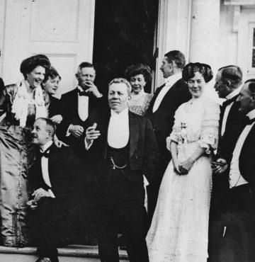 Historien om Losby Gods. Festkledde og feststemte mennesker på trappen utenfor gamlegodset